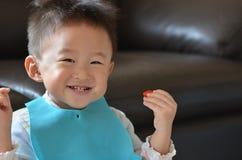 Szczęśliwa chłopiec je truskawki zdjęcia stock