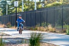 Szczęśliwa chłopiec jedzie jego bicykl na roweru pasie ruchu zdjęcie royalty free