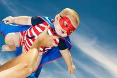 Szczęśliwa chłopiec jest ubranym bohatera kostiumu latanie obrazy stock