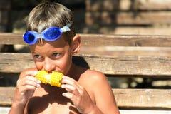Szczęśliwa chłopiec jest ubranym pływackich gogle je kukurudzę na cob Lato weekend zdjęcie stock