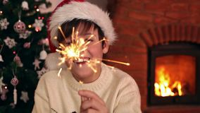 Szczęśliwa chłopiec jest ubranym Santa kapelusz i trzyma bożego narodzenia sparkler zbiory wideo