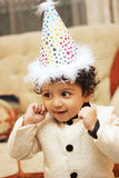 Szczęśliwa chłopiec jest ubranym urodzinowego kapelusz i świętuje jego urodziny zdjęcie royalty free