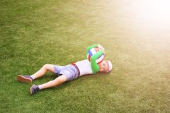 Szczęśliwa chłopiec kłama na boisku piłkarskim z piłką zdjęcie royalty free