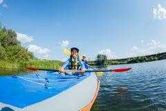 Szczęśliwa chłopiec kayaking na rzece na słonecznym dniu podczas wakacje Zdjęcie Royalty Free