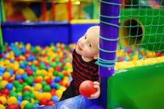 Szczęśliwa chłopiec ma zabawę w balowej jamie z kolorowymi piłkami zdjęcia royalty free
