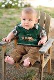 Szczęśliwa chłopiec na drewnianym krześle ogrodowym Fotografia Royalty Free