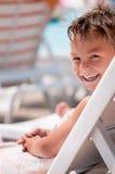 Szczęśliwa chłopiec na pokładu krześle Obraz Royalty Free