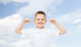 Szczęśliwa chłopiec napina bicepsy w białej koszulce Zdjęcia Stock