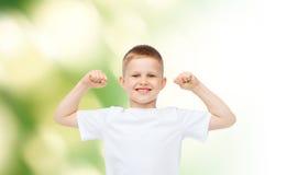 Szczęśliwa chłopiec napina bicepsy w białej koszulce Obraz Stock