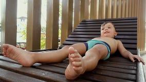 Szczęśliwa chłopiec odpoczywa na lounger po pływać zdjęcie wideo