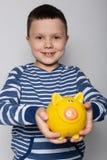 Szczęśliwa chłopiec ono uśmiecha się i trzyma za jego rękach z prosiątko bankiem, finanse i oszczędzania pojęciem, fotografia stock