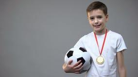 Szczęśliwa chłopiec ono uśmiecha się z zwycięzcy medalem na klatce piersiowej, trzyma piłki nożnej piłkę, mistrz zbiory