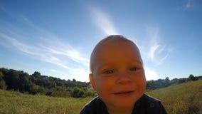 Szczęśliwa chłopiec patrzeje w kamerze i dotyka je plenerowego Śliczny dziecko dotyka obiektyw kamera wideo i ono uśmiecha się pr zbiory