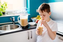 Szczęśliwa chłopiec pije selfmade owocowego koktajl Zdjęcia Royalty Free