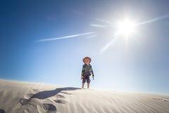 Szczęśliwa chłopiec pozycja na szczyciefal tg0 0n w tym stadium wietrznej piasek diuny na opóźnionym su obrazy royalty free