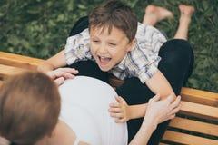 Szczęśliwa chłopiec przytulenia matka w parku przy dnia czasem Zdjęcia Stock
