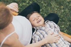Szczęśliwa chłopiec przytulenia matka w parku przy dnia czasem Zdjęcia Royalty Free