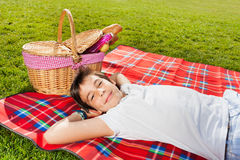 Szczęśliwa chłopiec relaksuje na pinkinie obok koszałki obrazy stock