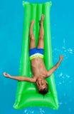 Szczęśliwa chłopiec relaksuje na zielonej nadmuchiwanej materac Zdjęcie Stock