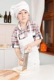 Szczęśliwa chłopiec robi pizzy ciastu fotografia royalty free