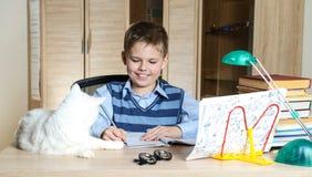 Szczęśliwa chłopiec robi pracie domowej z kotem i książkami na stole jest edukacja starego odizolowane pojęcia Obrazy Stock
