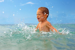 Szczęśliwa chłopiec robi wodnym pluśnięciom w morzu Obrazy Royalty Free
