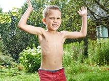 Szczęśliwa chłopiec skacze pod deszczem Zdjęcia Royalty Free