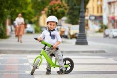Szczęśliwa chłopiec w białej hełm przejażdżce jego pierwszy rower zdjęcia royalty free