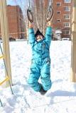 Szczęśliwa chłopiec w ciepłych całkowitych sztukach outdoors w zimie obraz stock
