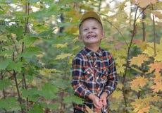 Szczęśliwa chłopiec w jesień lesie Obrazy Royalty Free