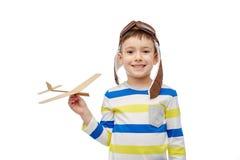 Szczęśliwa chłopiec w lotnika kapeluszu z samolotem Zdjęcia Royalty Free