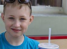 Szczęśliwa chłopiec w miasto kawiarni na ulicie obraz stock