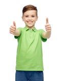 Szczęśliwa chłopiec w zielonej polo koszulce pokazuje aprobaty zdjęcia royalty free