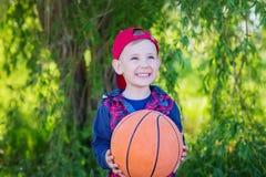 Szczęśliwa chłopiec wręcza koszykówkę, zdjęcie royalty free
