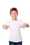 Szczęśliwa chłopiec wskazuje jego dotyka na pustej koszulce, plac zdjęcie stock