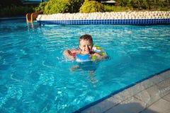 Szczęśliwa chłopiec z błękitnym życie pierścionkiem zabawę w pływackim basenie w kurort zdjęcie royalty free