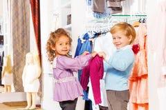 Szczęśliwa chłopiec z dziewczyna chwyta jaskrawym pulowerem i spojrzeniem Fotografia Stock