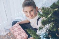 Szczęśliwa chłopiec z jego Bożenarodzeniowym prezentem Boże Narodzenia, wakacje i prezenty, zdjęcie royalty free