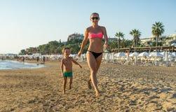 Szczęśliwa chłopiec z młodym pięknym macierzystym bieg na lato plaży Pozytywne ludzkie emocje, uczucia, radość Śmieszny śliczny d Obrazy Stock