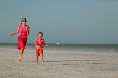 Szczęśliwa chłopiec z macierzystym bieg na lato plaży Zdjęcie Stock