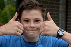 Szczęśliwa chłopiec z oba aprobatami obraz stock