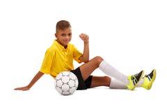 Szczęśliwa chłopiec z piłki nożnej piłką Rozochocony dziecko w futbolowym mundurze odizolowywającym na białym tle Sporta pojęcie fotografia royalty free