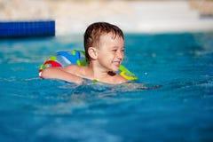 Szczęśliwa chłopiec z różnobarwnym życie pierścionkiem zabawę w pływackim basenie w kurort fotografia stock