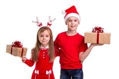 Szczęśliwa chłopiec z Santa kapeluszem na jego głowie i dziewczynie z jelenimi rogami, trzyma prezentów pudełka w ich rękach Poję zdjęcia royalty free