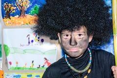 Szczęśliwa chłopiec z twarzą malował z węglem drzewnym Cos i afro peruką Obraz Stock
