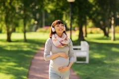 Szczęśliwa ciężarna azjatykcia kobieta w hełmofonach przy parkiem Zdjęcie Stock