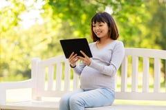 Szczęśliwa ciężarna azjatykcia kobieta z pastylka komputerem osobistym przy parkiem Obrazy Royalty Free