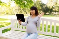 Szczęśliwa ciężarna azjatykcia kobieta z pastylka komputerem osobistym przy parkiem Obraz Stock