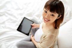 Szczęśliwa ciężarna azjatykcia kobieta z pastylka komputerem osobistym w domu Zdjęcia Stock