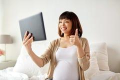 Szczęśliwa ciężarna azjatykcia kobieta z pastylka komputerem osobistym w domu Fotografia Royalty Free
